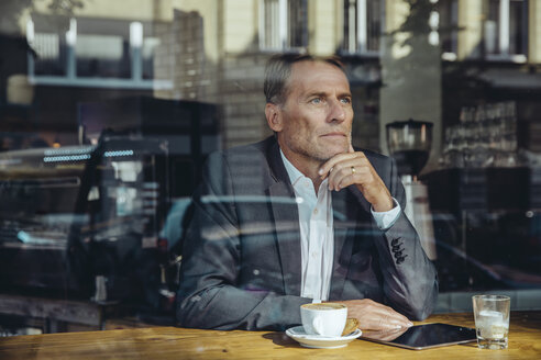 Serious businessman in cafe looking out of window - MFF03869