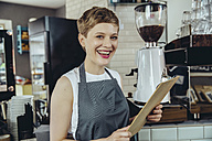 Portrait of laughing waitress holding menu in a cafe - MFF03872