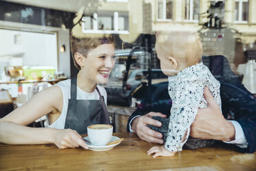 Waitress serving coffee to smiling customer with baby in cafe - MFF03878