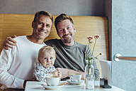 Portrait of happy gay couple with their baby in cafe - MFF03884
