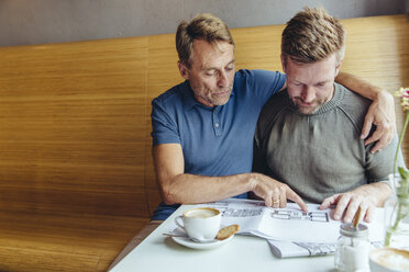 Gay couple looking at constructions plans for their home in cafe - MFF03893