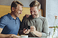 Excited gay couple with wedding ring in cafe - MFF03896
