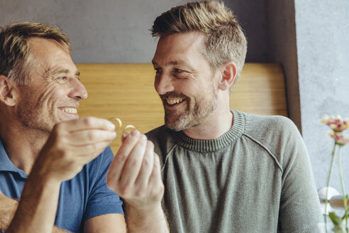 Happy gay couple holding up their wedding rings - MFF03899
