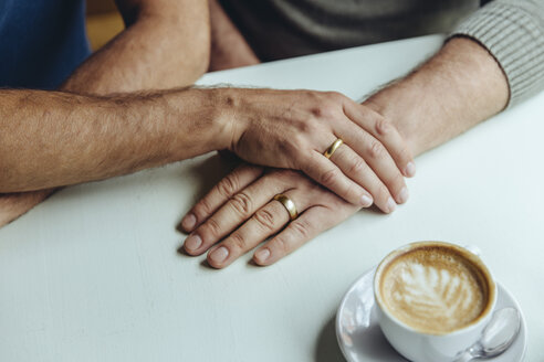 Close-up of men's hands with wedding rings and a cup of coffee - MFF03902