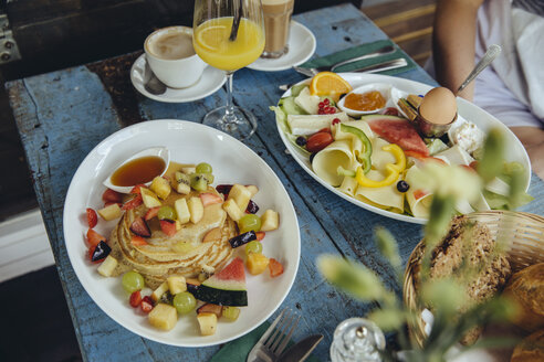 Plates with pancakes and fruit and vegetarian breakfast at cafe - MFF03917