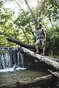Young man standing on log at a waterfall in forest - VPIF00032