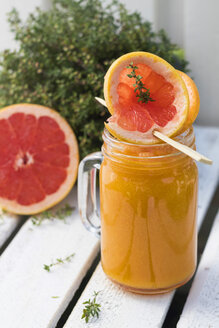 Glass of fruit smoothie with Pink Grapefruit, orange, mango and thyme - YFF00678