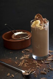 Glass of cocoa smoothie with banana, avocado, cocoa and chocolate chips - YFF00681