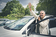 Portrait of smiling mature businessman waving while entering his car - JUNF00886