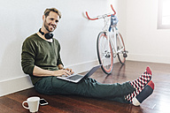 Portrait of smiling man with headphones sitting on the floor at home using laptop - GIOF03166