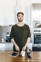 Portrait of man standing in kitchen raising his eyebrows - GIOF03169
