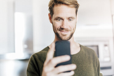 Portrait of smiling man looking at cell phone - GIOF03172