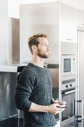 Pensive man standing in kitchen with cell phone and glass of water - GIOF03175