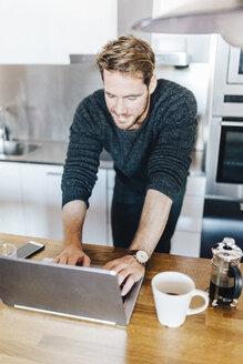 Smiling man standing in kitchen using laptop - GIOF03178
