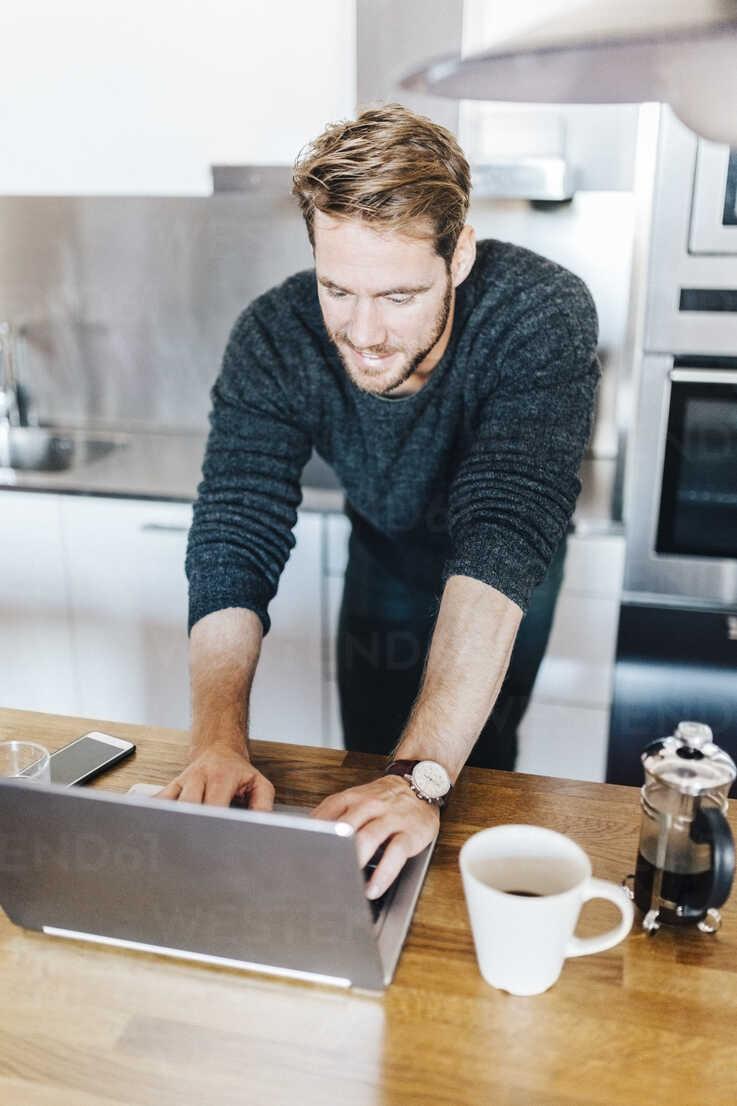 Smiling man standing in kitchen using laptop - GIOF03178 - Giorgio Fochesato/Westend61