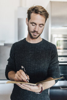 Portrait of man writing in notebook in the kitchen - GIOF03181