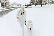 Young woman going walkies with her dog in the snow - ZEDF00824
