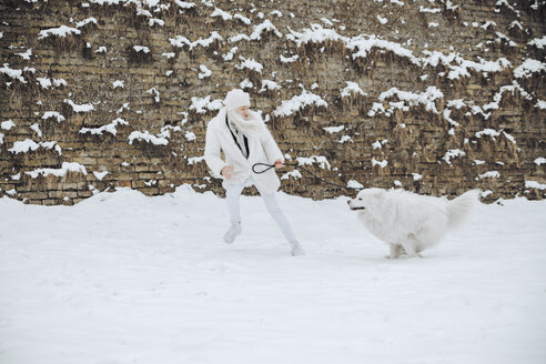 Young woman playing with her dog in the snow - ZEDF00830