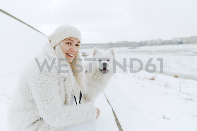 Portrait of white dressed smiling young woman with her white dog in the snow - ZEDF00833
