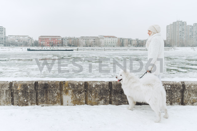 Serbia, Petrovaradin, white dressed young woman standing with white dog in the snow at riverside - ZEDF00836
