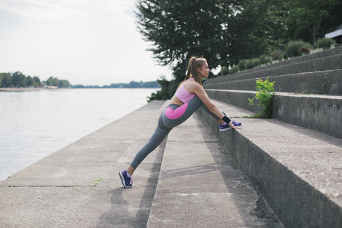 Young woman stretching at the riverbank - MOMF00231
