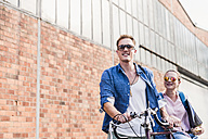 Young couple with bicycle and sunglasses on the move - UUF11518