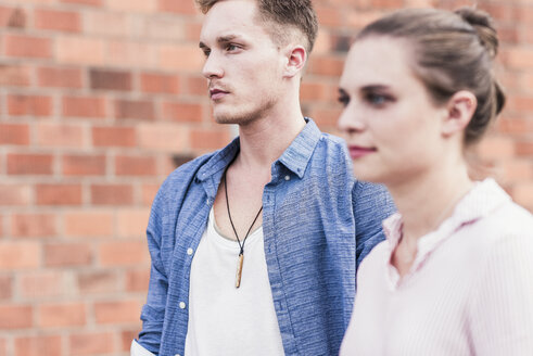 Young couple in front of brick wall - UUF11524