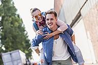 Young man giving girlfriend piggyback ride - UUF11527