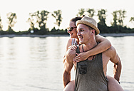 Young man giving girlfriend piggyback ride at the riverbank - UUF11536