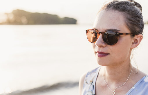 Young woman wearing sunglasses at the riverbank - UUF11545