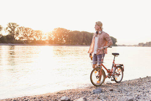Young man walking with bicycle at the riverbank at sunset - UUF11554