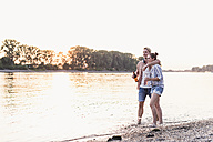 Young couple wading in river at sunset - UUF11557