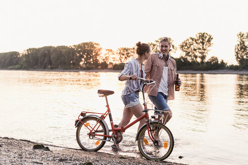 Young couple with bicycle wading in river - UUF11560