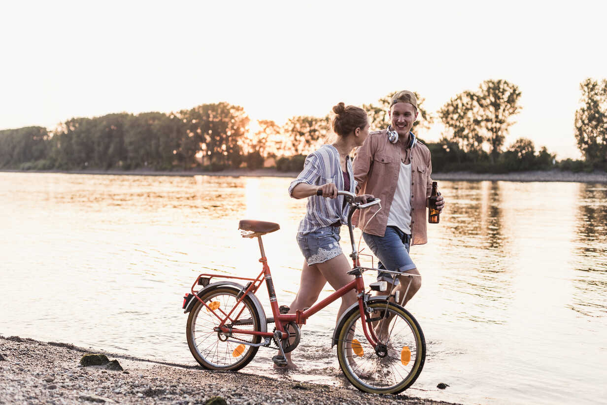 Young couple with bicycle wading in river - UUF11560 - Uwe Umstätter/Westend61
