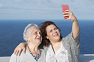 Grandmother and granddaughter taking a selfie in front of the sea - RAEF01933