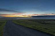 UK, Scotland, Caithness, Duncansby Head, rural road at sunset - FOF09288