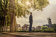 Netherlands, Venlo, businessman standing on pavement looking around - KNSF02404