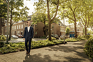 Netherlands, Venlo, confident businessman standing on pavement - KNSF02407