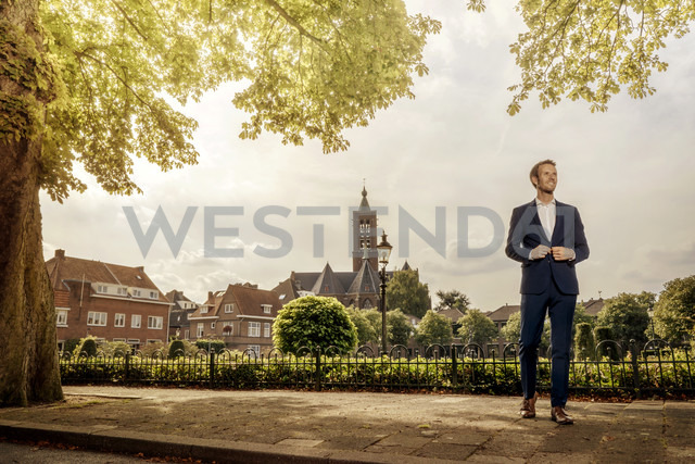 Netherlands, Venlo, businessman standing on pavement - KNSF02410