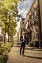 Netherlands, Venlo, businessman with cell phone walking on pavement - KNSF02413