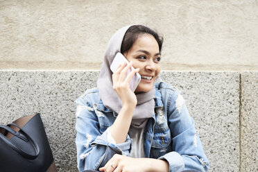 Young woman wearing hijab on cell phone - IGGF00121