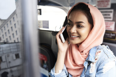 UK, England, London, young woman wearing hijab on the phone in a taxi - IGGF00130