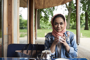 Young woman wearing hijab holding a cup on a terrace of a cafe - IGGF00133