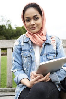 Young woman wearing hijab holding laptop sitting in a bench - IGGF00136