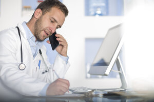 Doctor at desk talking on cell phone - ZEF14512