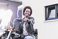 Portrait of smiling young woman with her motorcycle - UUF11569