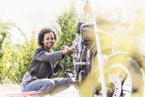 Young woman cleaning her motorcycle - UUF11572