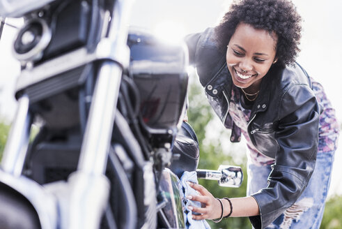 Young woman cleaning her motorcycle - UUF11575