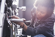 Young woman maintaining her motorcycle - UUF11578