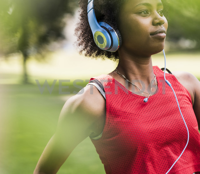 Sporty young woman with headphones in park - UUF11584